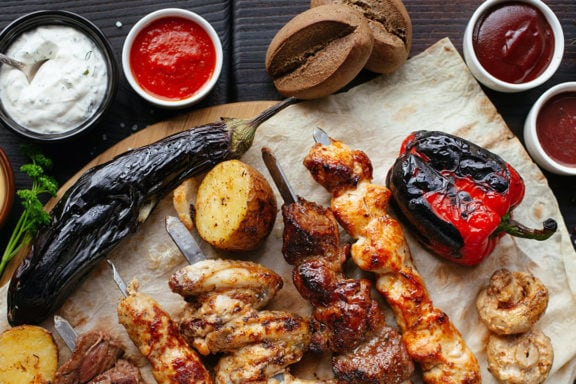 Skewered meat on a table with different hot sauces and dips in ramekins