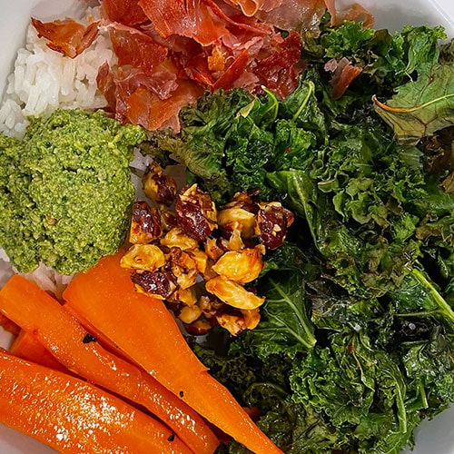 rice topped with roasted kale, carrots, proscuitto, hazelnuts, and basil pesto in a bowl